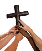 Several hands holding up steel cross