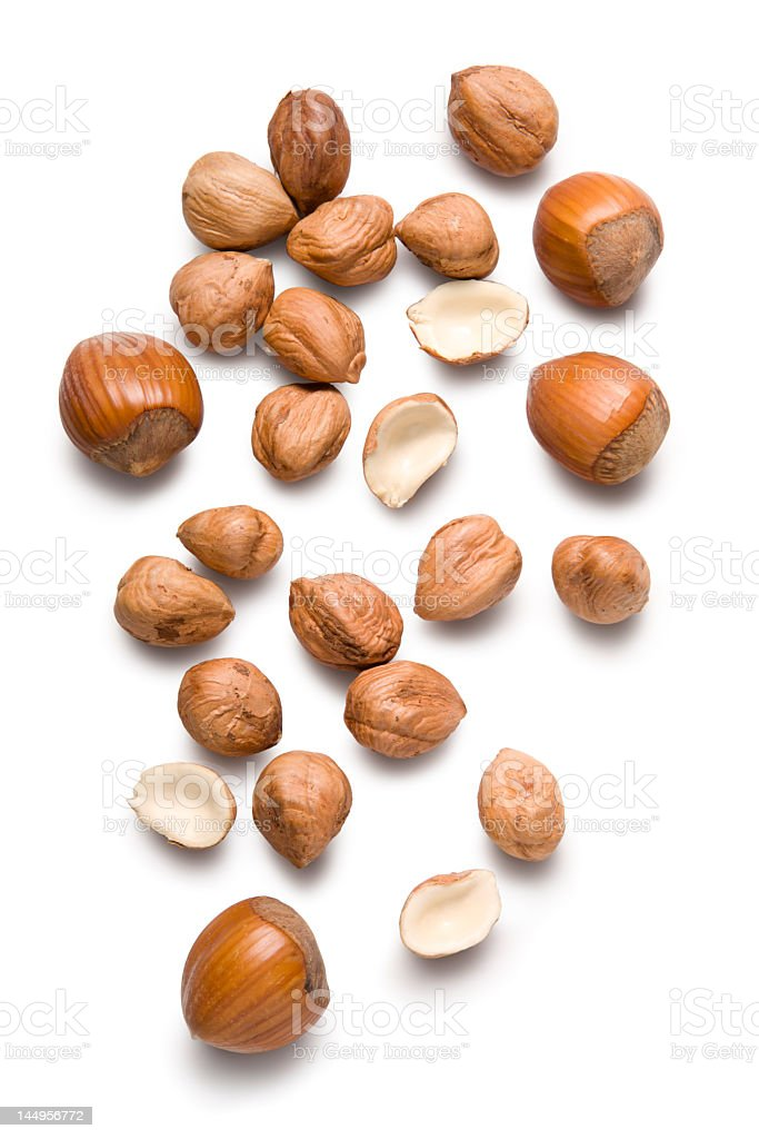 Several hazelnuts lying on a white surface royalty-free stock photo