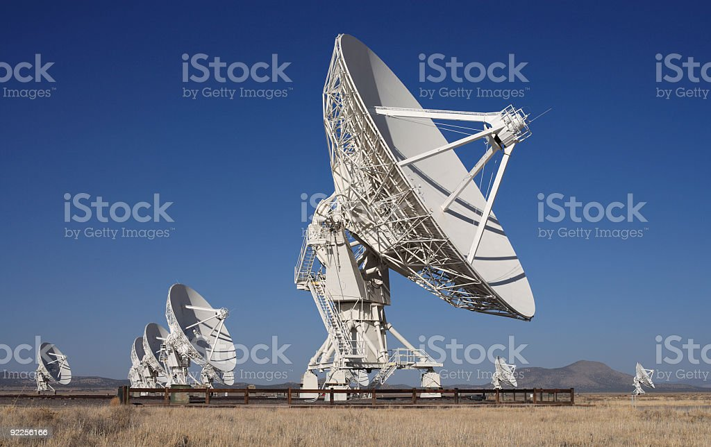Several huge radio telescopes out in a desert pointed at sky stock photo