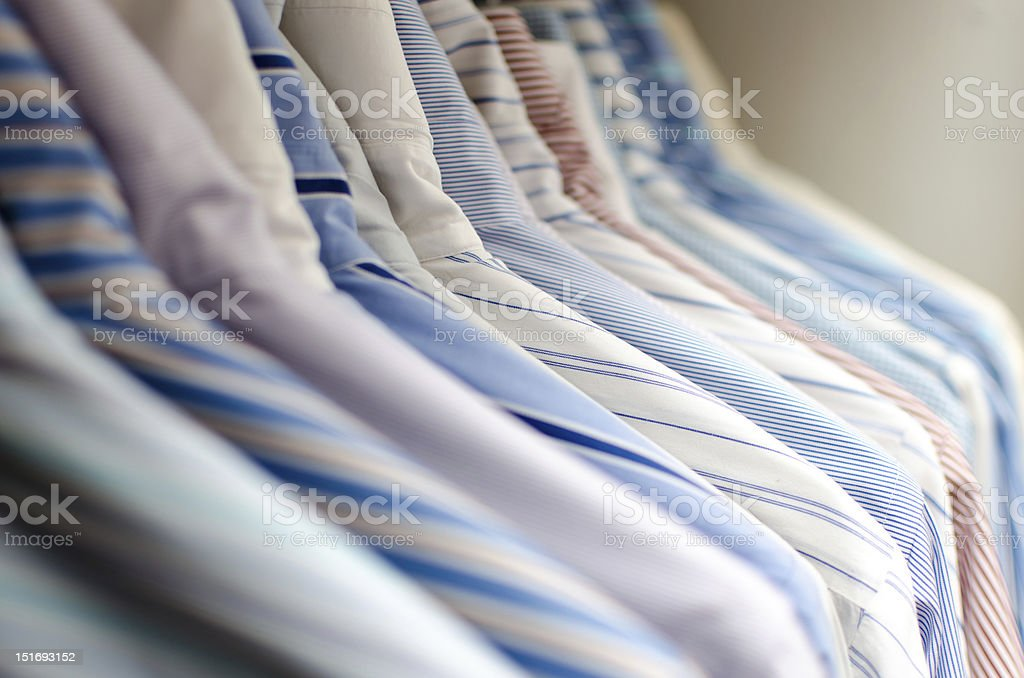 Several ironed mens shirts in a wardrobe stock photo
