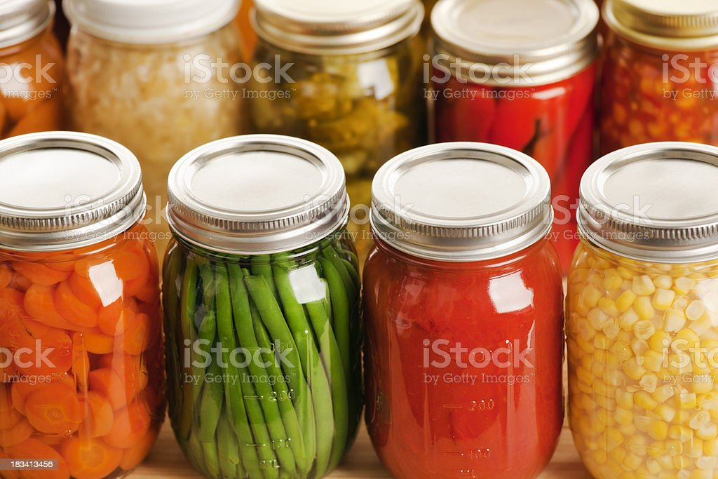 Several jars of harvest vegetables in rows stock photo