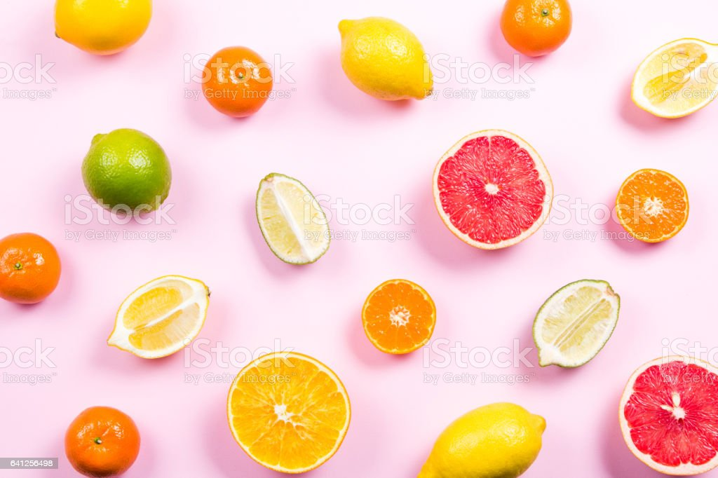 Several kinds of whole and cut citrus on a pink background stock photo