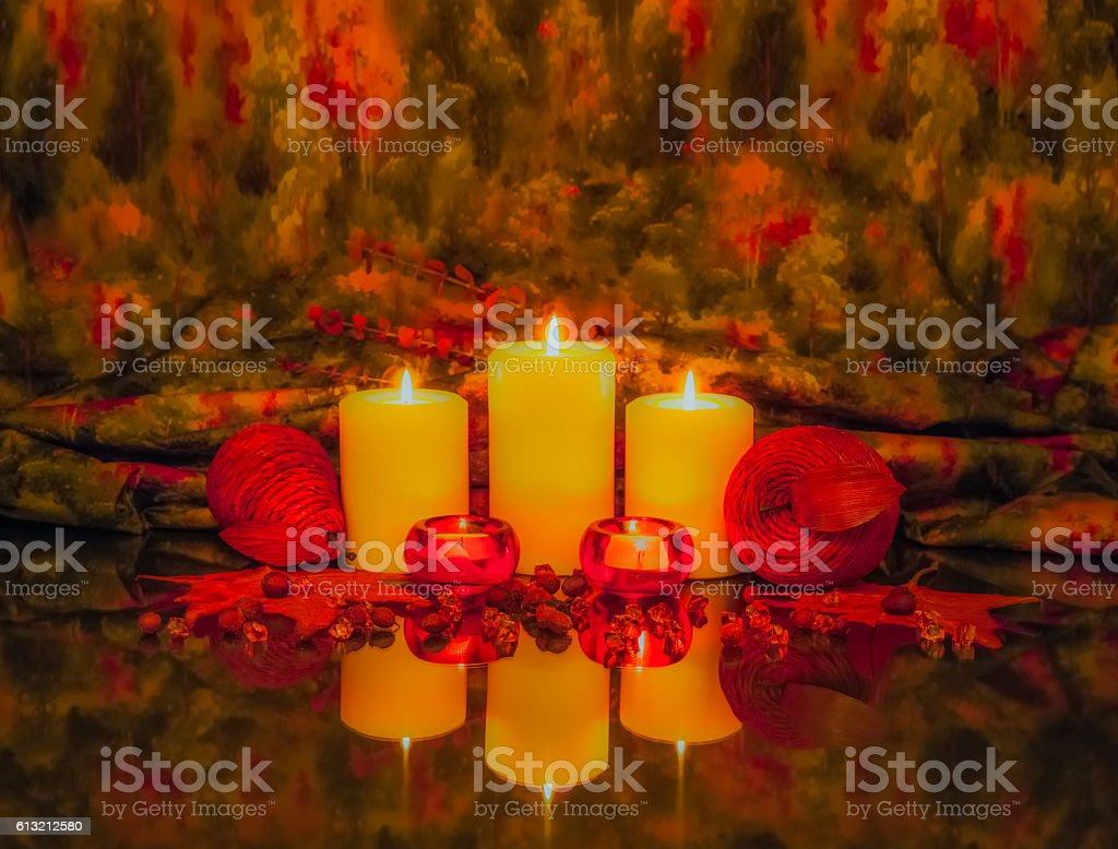 Several lit candles are reflected  in fall colors (P) stock photo