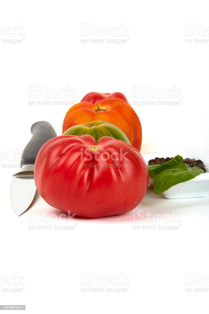 Several organic tomatoes in series with a knife royalty-free stock photo