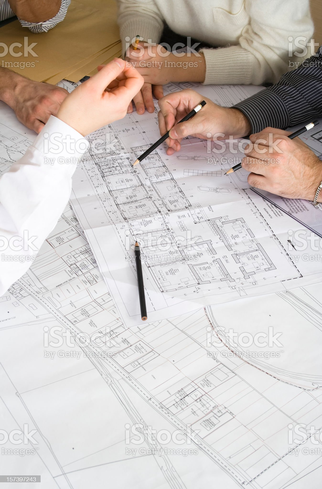 Several pairs of hands working together on blueprints royalty-free stock photo