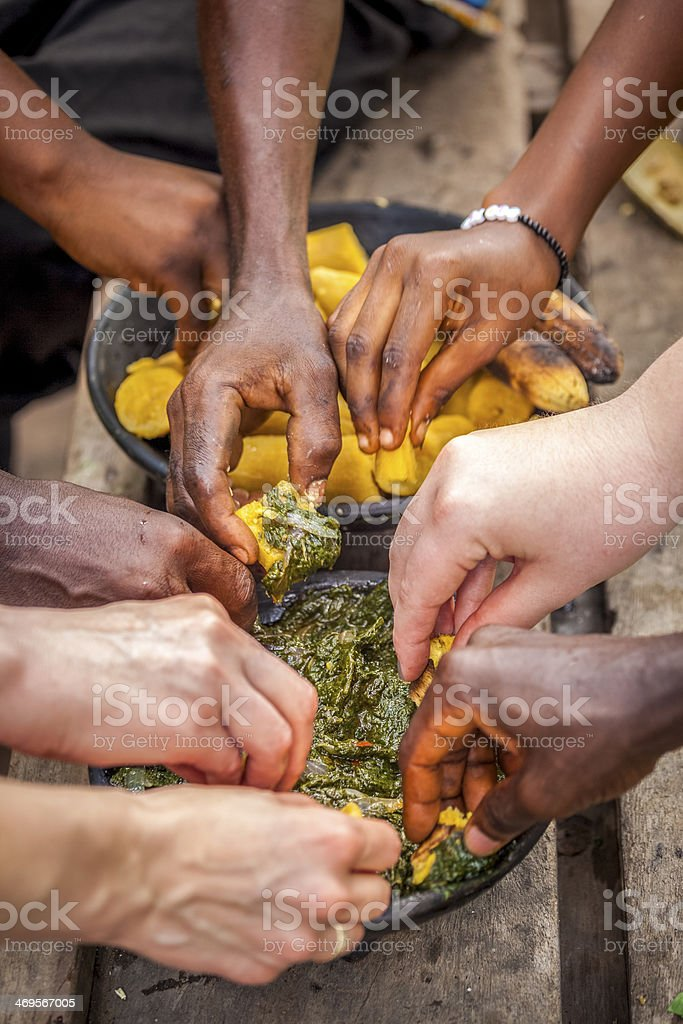 Several people eating African food stock photo