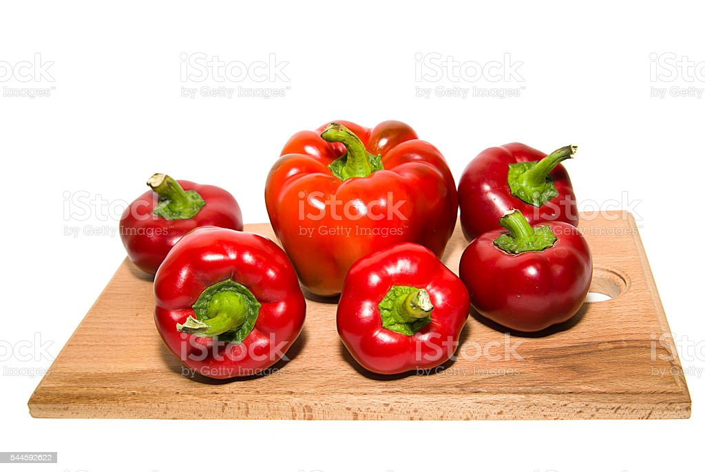 Several  peppers on a wooden cutting board. stock photo
