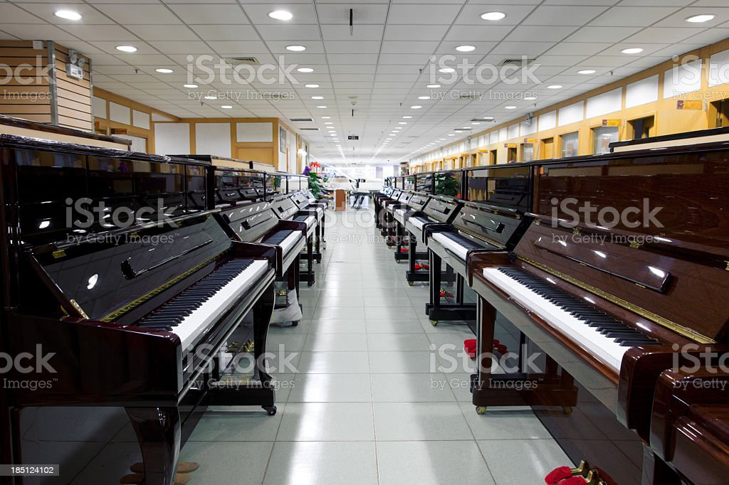 Several pianos lined up in a music store stock photo