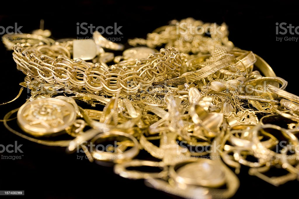 Several pieces of gold jewelry in a pile stock photo