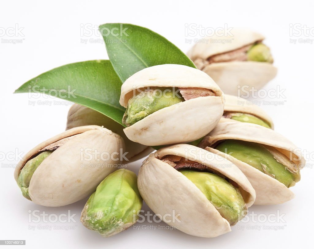 Several pistachio nuts against white background stock photo