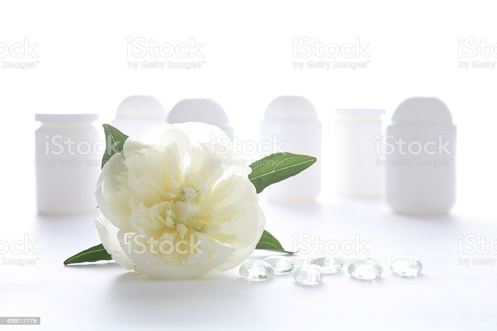several plastic cosmetic jars with white peony and glass drops stock photo
