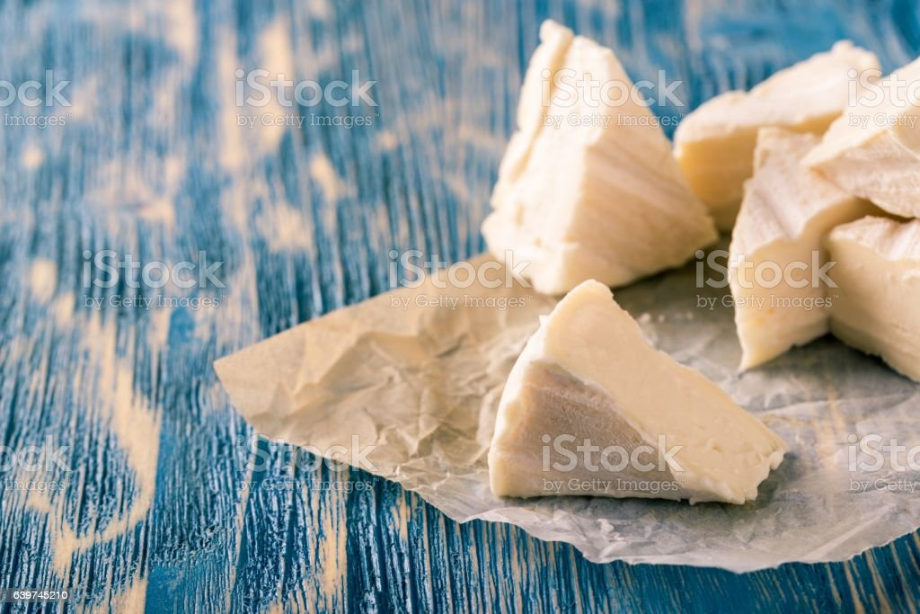 Several portions of camembert cheese on blue wooden board stock photo