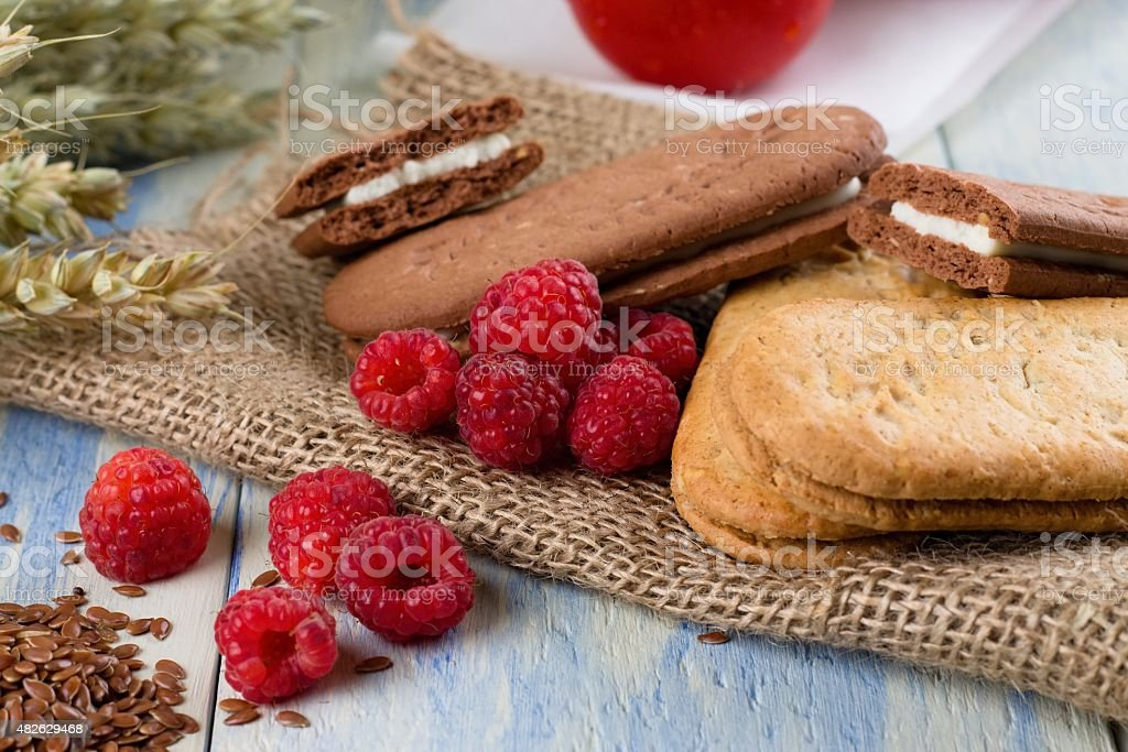 Several raspberries next to creame biscuits stock photo