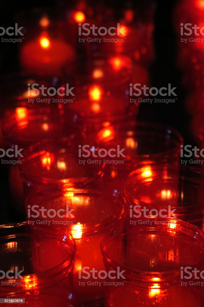 Several red glass religious  votive candles in a church stock photo