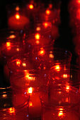 Several red glass religious  votive candles in a church