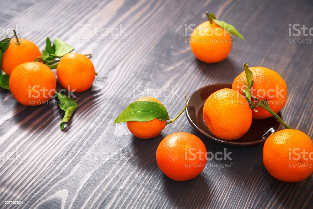 Several ripe tangerines on a wooden table stock photo