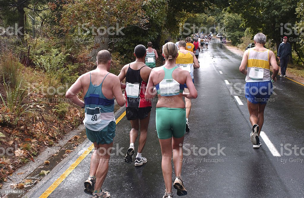 Several runners on a marathon running on a paved road stock photo