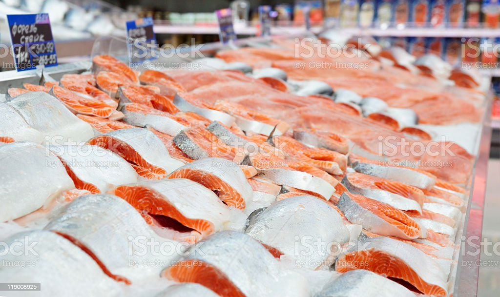 Several slices of salmon displayed on a market counter stock photo