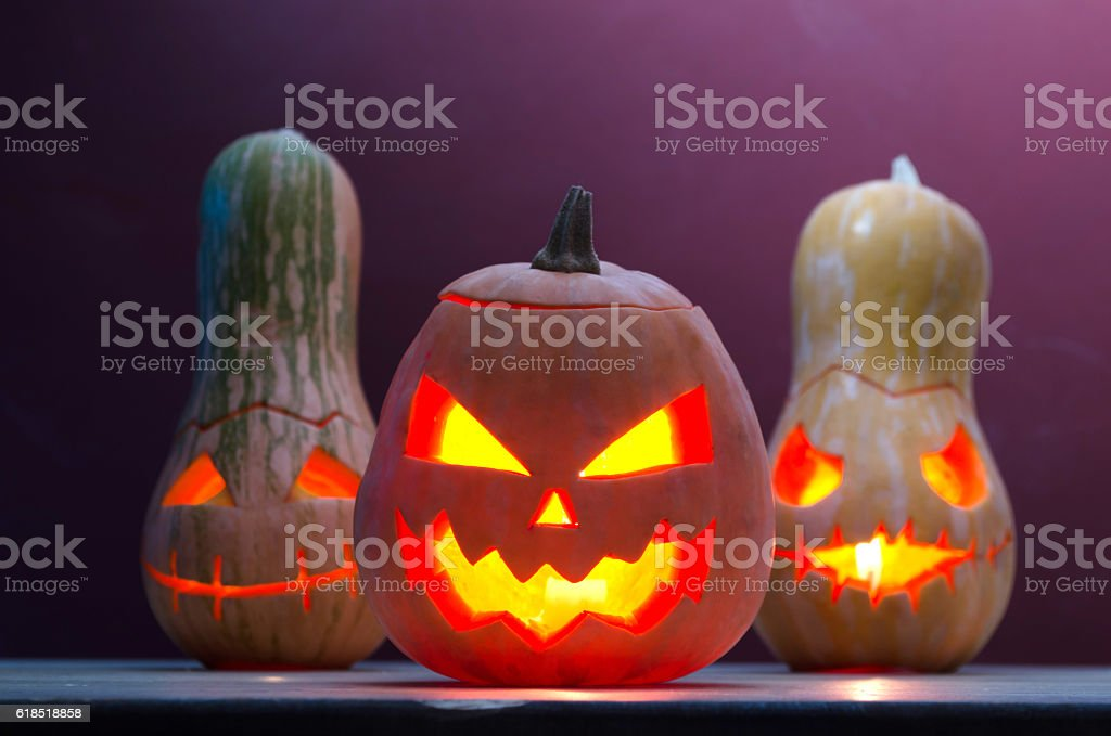 Several smiling pumpkins with candles, Halloween. stock photo