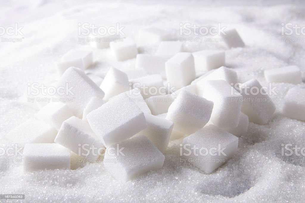 Several sugar cubes on sugar grains stock photo