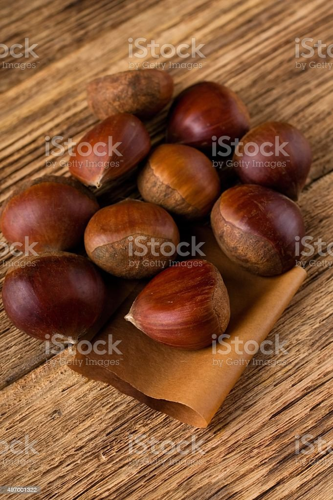 Several sweet chestnuts on wooden board stock photo