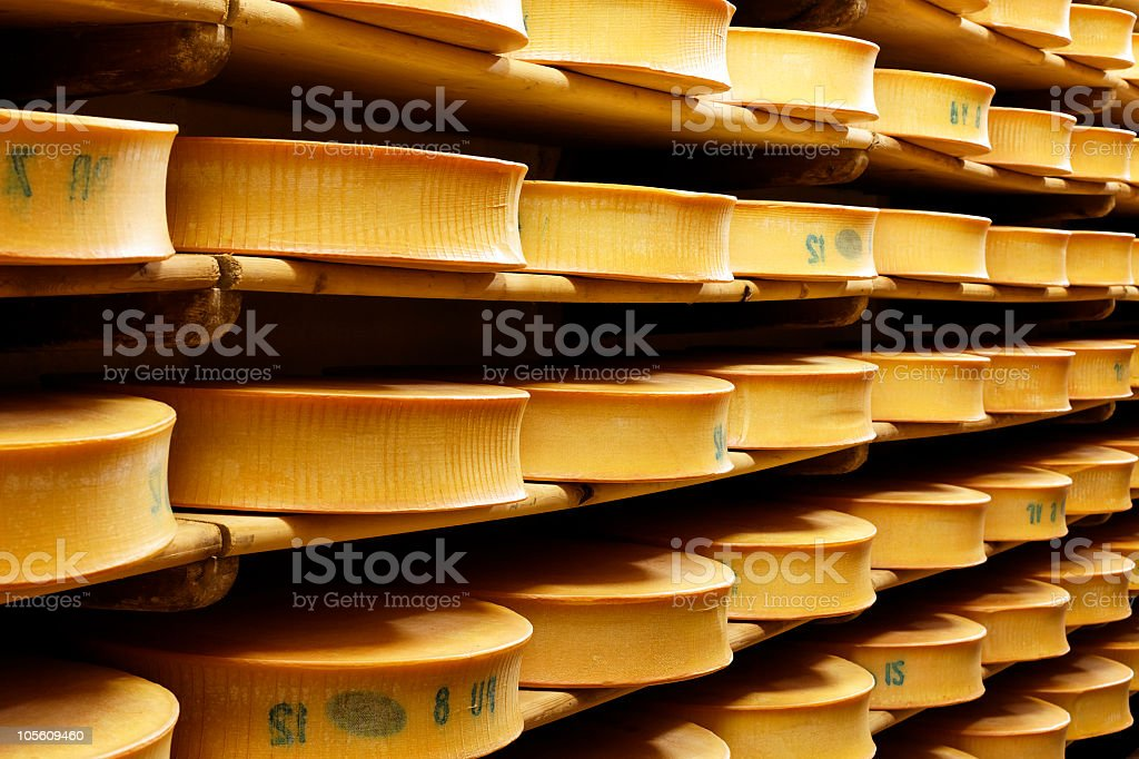 Several tan-colored shelves full of yellow French cheeses stock photo