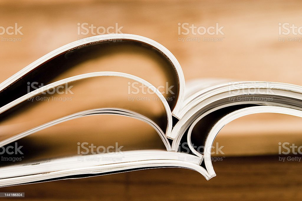 Several thin books stacked together and laying open stock photo
