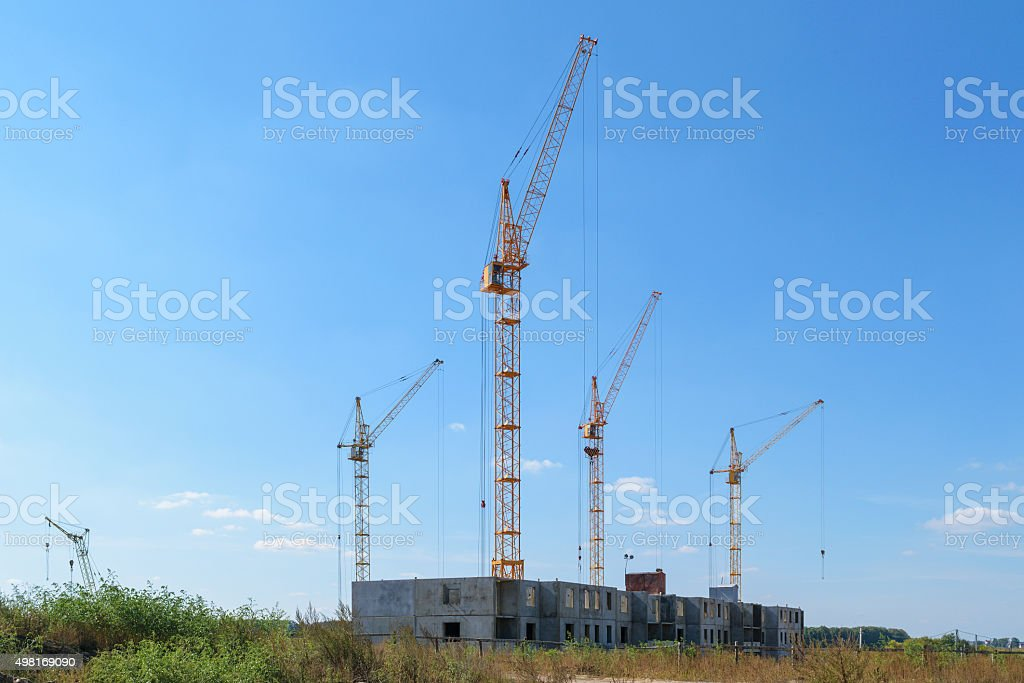 Several tower cranes building a new multi-storey panel house stock photo
