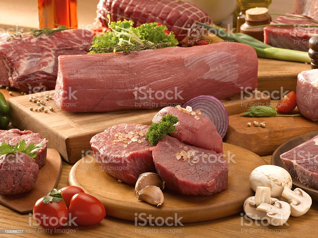 Several types of raw meat on display with spice & vegetables stock photo