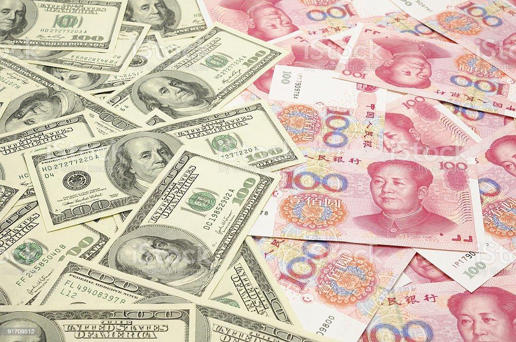 Several US dollar bills next to several Chinese yuan bills stock photo