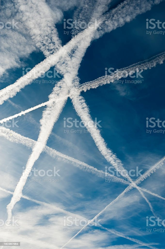 Several vapor trails crossing in the sky stock photo