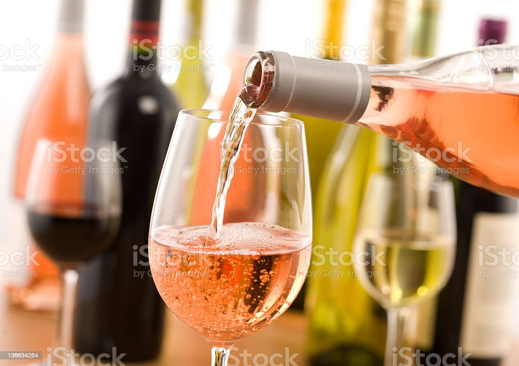Several varieties of wine behind a rose being poured stock photo