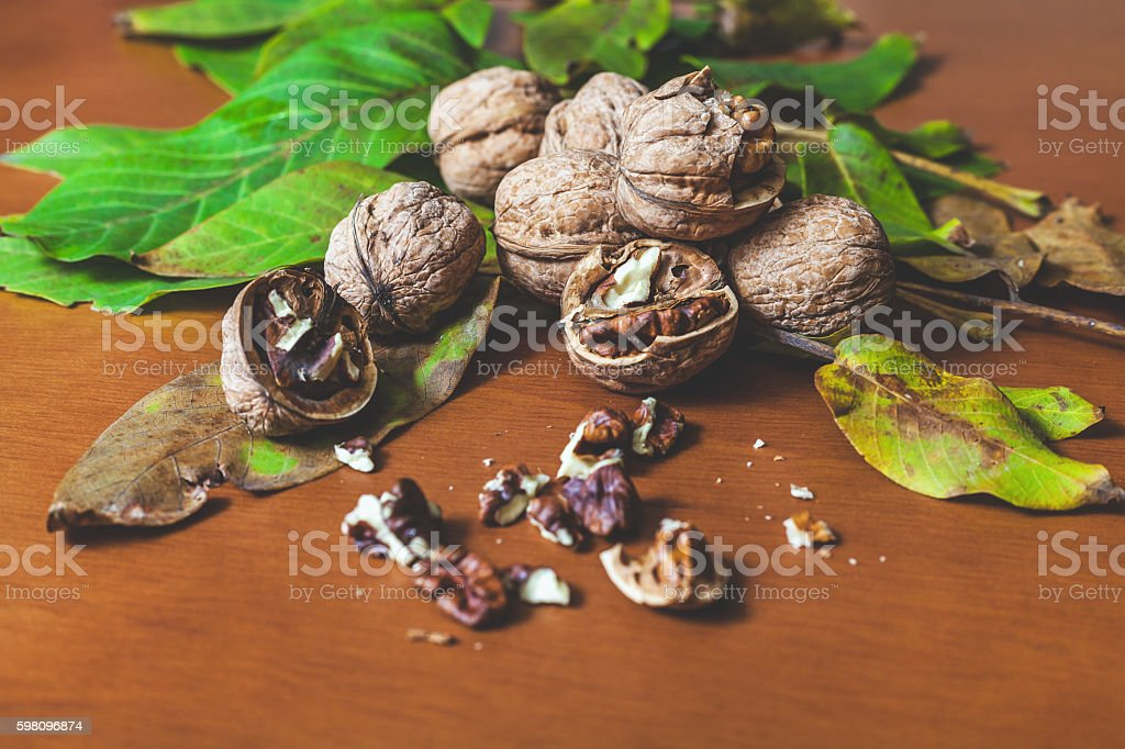 Several walnut kernels and lie on  brown background stock photo