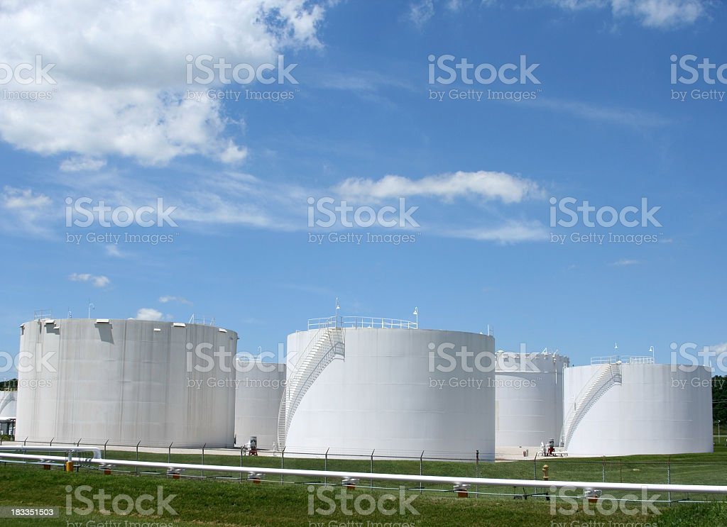 Several white storage tanks in a grassy field stock photo