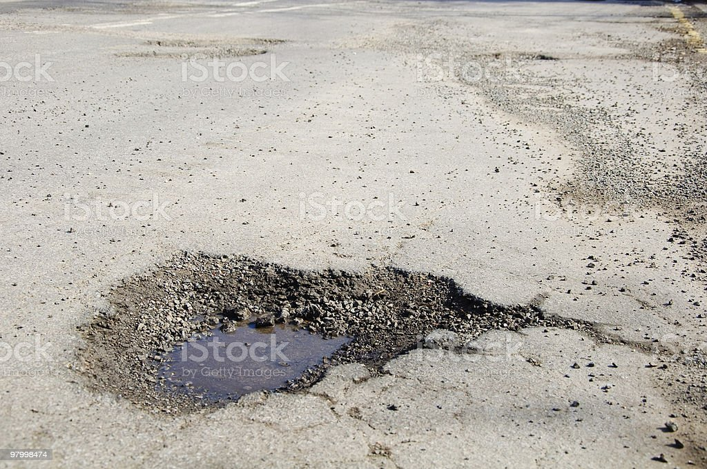 Severe pothole damage in a main road stock photo