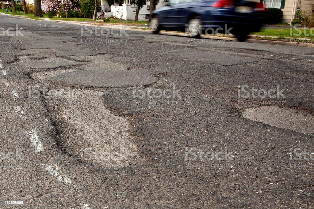 Severely potholed suburban road, close-up of potholes royalty-free stock photo