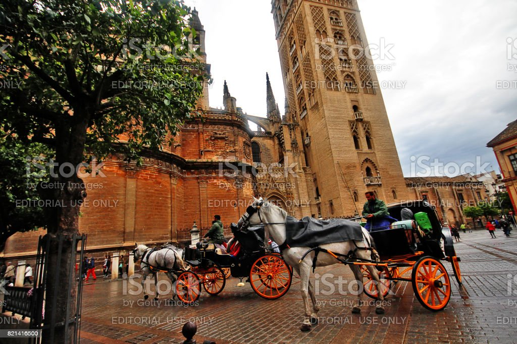 Seville (Sevilla), Andalusia, Southern Spain - March 14, 2017 - Horse carriage with Giralda (Torre de la Giralda) at Plaza Virgen de Los Reyes stock photo
