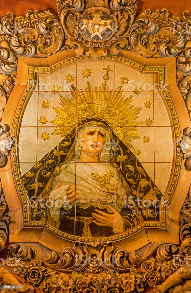 Seville - The ceramic tiled, cried Madonna stock photo