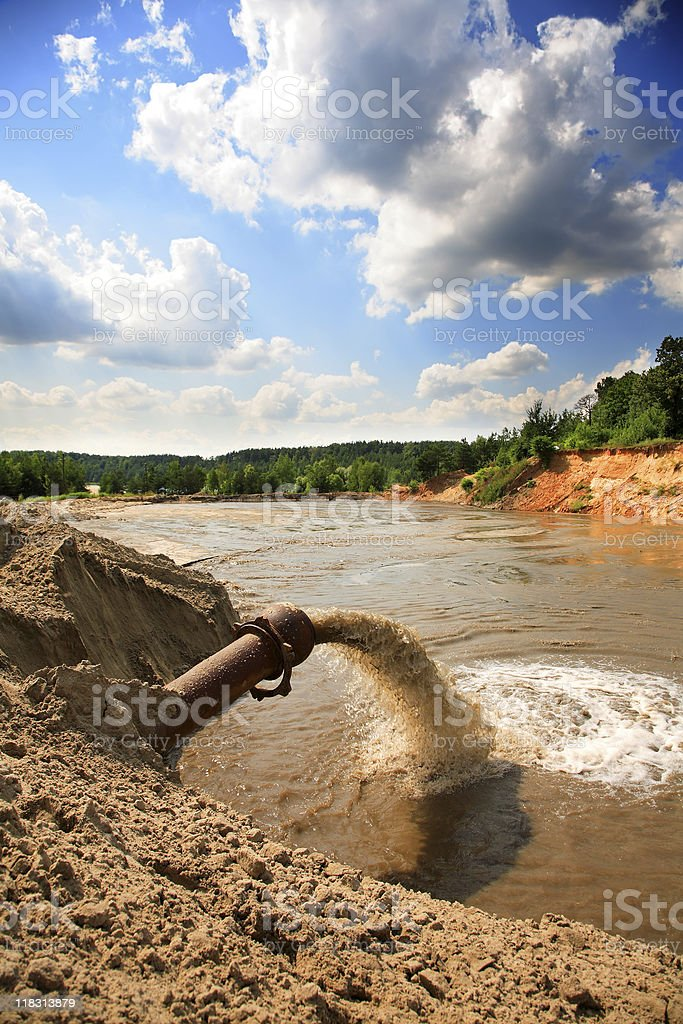 sewage flowing from a pipe in the river royalty-free stock photo