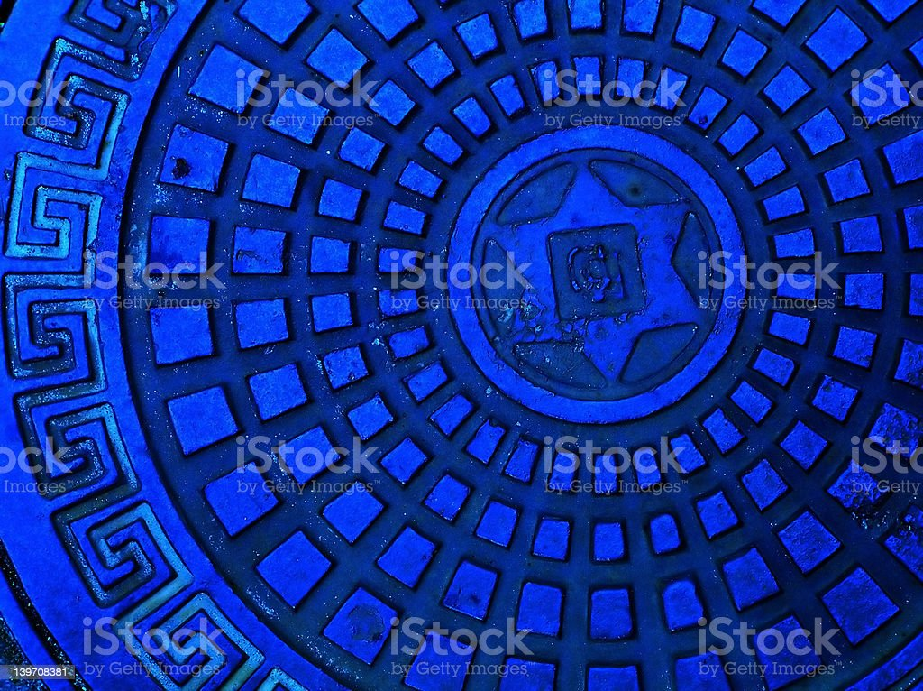 Sewer cap in blue color with meander pattern stock photo