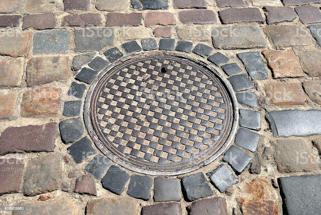 Sewer manhole cover old cobblestone street stock photo