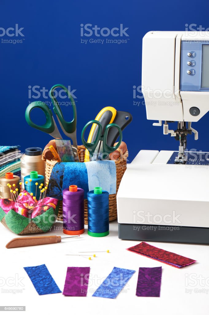 Sewing accessories in a basket and spools of threads next to sewing machine stock photo