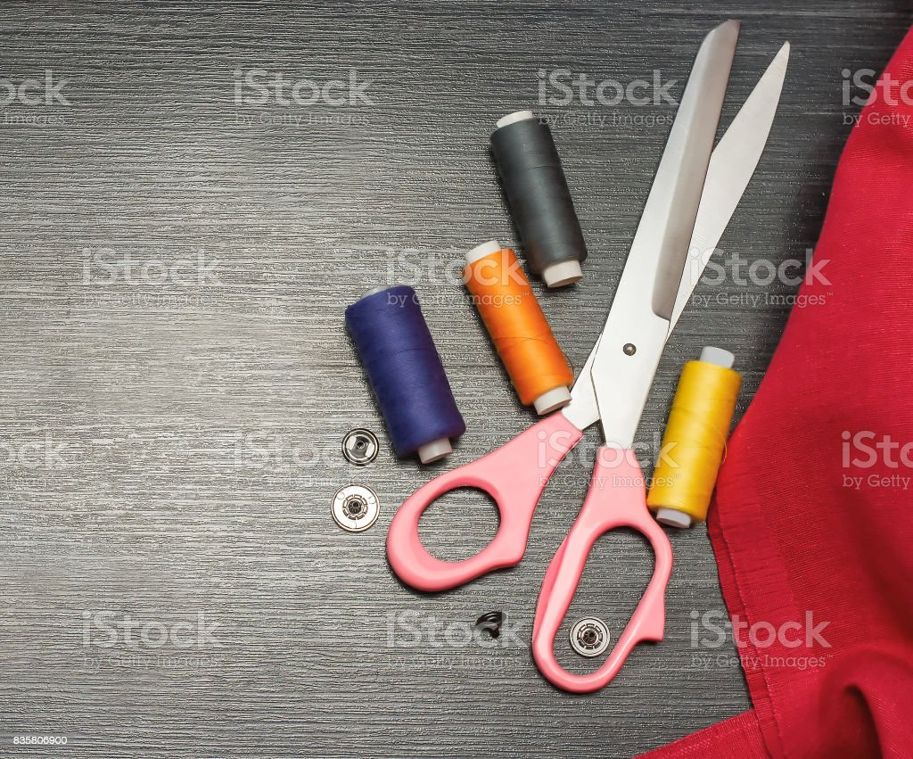 Sewing background: red cloth. cushion with needles  and  colorful threads on wooden table. Top view stock photo