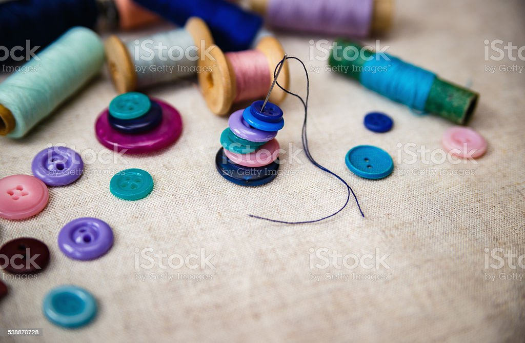 Sewing buttons and spools of threads on canvas stock photo