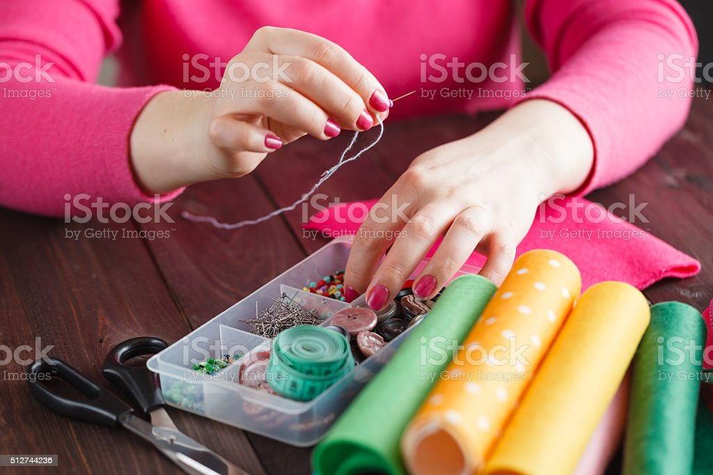Sewing craft needle textile thread in human finger stock photo