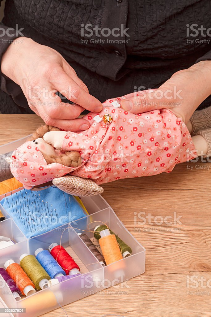 Sewing homemade rag doll stock photo