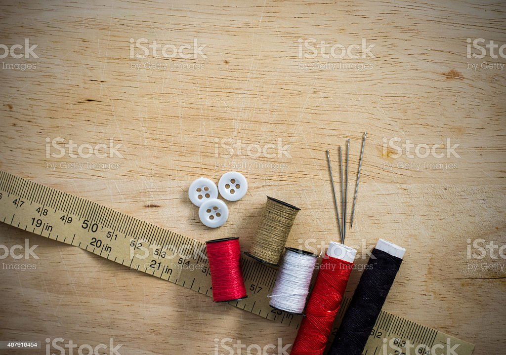 Sewing kit with thread and needles on the wooden background stock photo