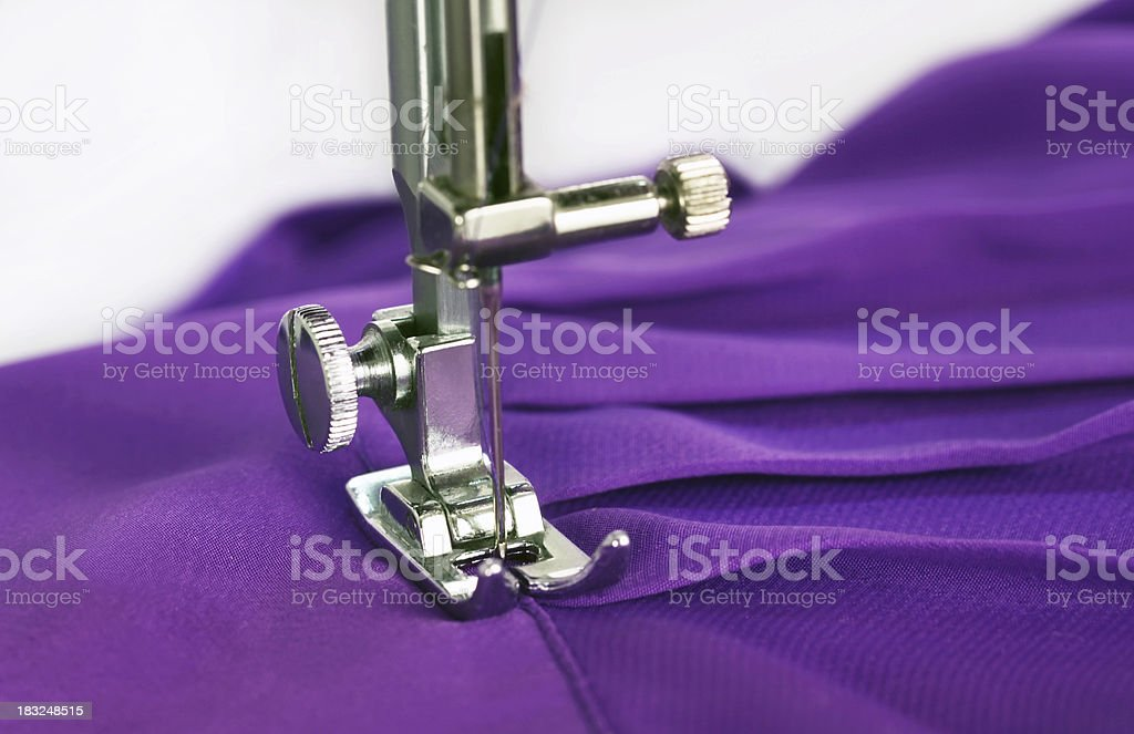 Sewing machine.  Mending purple silk blouse.  White background.  Close-up. royalty-free stock photo