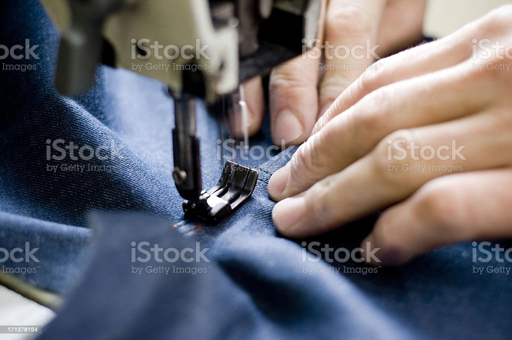 Sewing machine seeing on a blue fabric stock photo