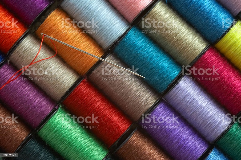 Sewing needle across different colored thread spools stock photo